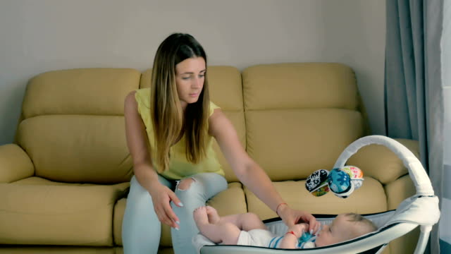 Young upset mother gives a dummy to a baby and rubs a temples from tiredness video
