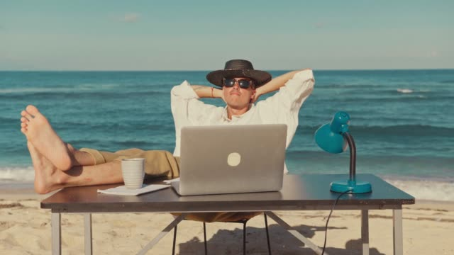 Young urban digital nomad of millennial generation z age sits on beach at resort or travel vacation destination, after work at laptop, resting putting his legs on table, remote office job, freelance