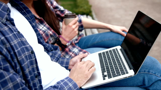 Young urban people  in checkered shirts and blue jeans using computer laptop and drinking coffee from to go cup on bench Young urban people  in checkered shirts and blue jeans using computer laptop and drinking coffee from to go cup on bench rocking chair stock videos & royalty-free footage