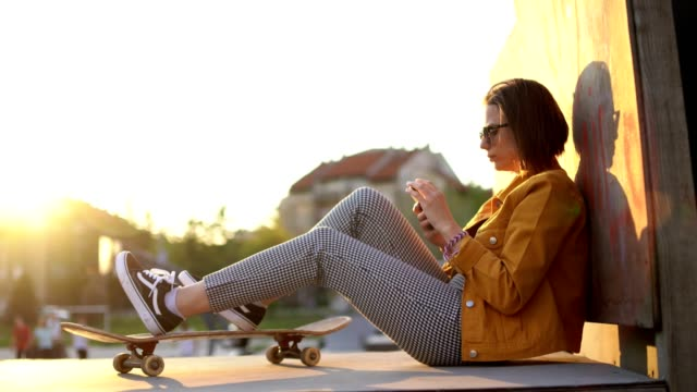 young urban woman using mobile at a skate park at sunset - miroslav mitic stock videos and b-roll footage