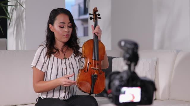 Young violinist teaching how to play violin online