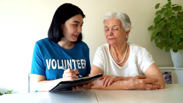 vídeos y material grabado en eventos de stock de joven voluntario haciendo una lista para la señora de edad - servicios sociales