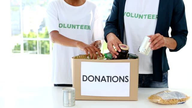 Young volunteer team packing a food donation box video