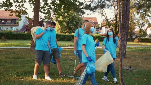 vídeos de stock, filmes e b-roll de jovens voluntários limpando lixo - voluntário