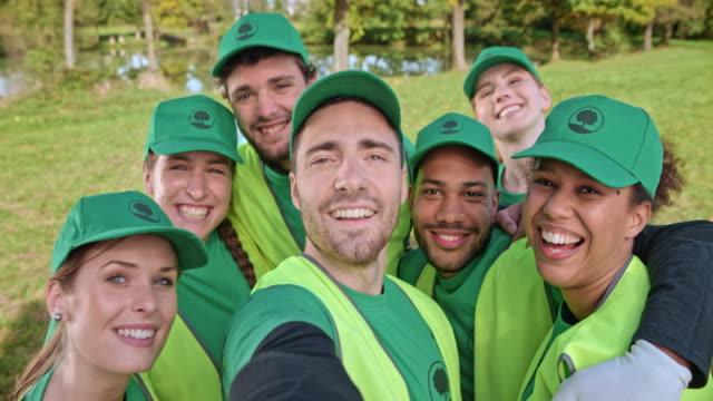 젊은 자원 봉사자는 깨끗 한-최대 이벤트는 selfie 햇볕이 잘 드는 풀밭에서 - 20 29세 스톡 비디오 및 b-롤 화면