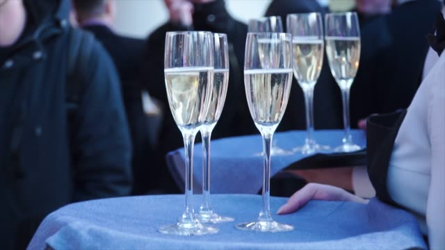 Young waitress carrying a tray with glasses of champagne. Clip. Professional waitress in uniform is serving champagne video