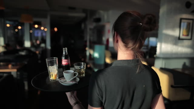 Young waitress serving drinks at beautiful rooftop cafe during sunny day video