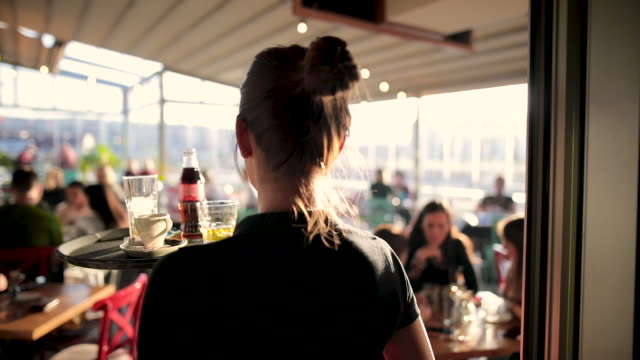 vídeos de stock e filmes b-roll de young waitress serving drinks at beautiful rooftop cafe during sunny day - servir comida e bebida