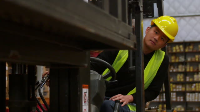 young warehouse worker operating forklift - azionare video stock e b–roll