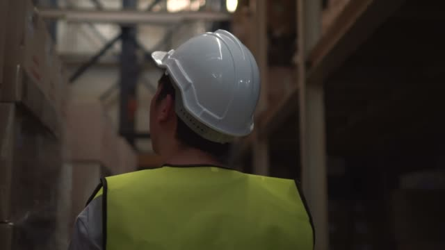 young warehouse worker with safety hard hat is walking through inventory room - irriducibilità video stock e b–roll