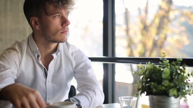 Young, well dressed, drinking coffee and looking through the window, while sitting in coffee bar video