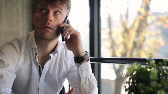 young, well dressed, man talking on the phone, shaking head, while sitting in coffee bar - solo un uomo giovane video stock e b–roll