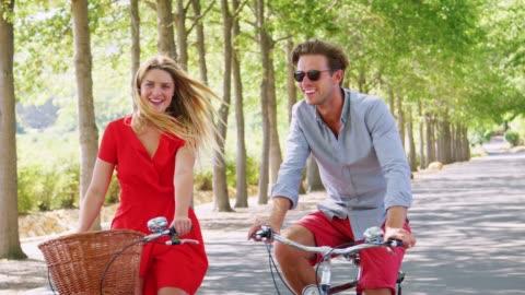 vidéos et rushes de blanc sans élevage en couple adultes à vélo sur une route bordée d'arbres - jeune couple