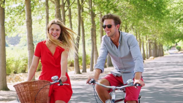 Young white adult couple riding bikes on a tree lined road Young white adult couple riding bikes on a tree lined road young couple stock videos & royalty-free footage