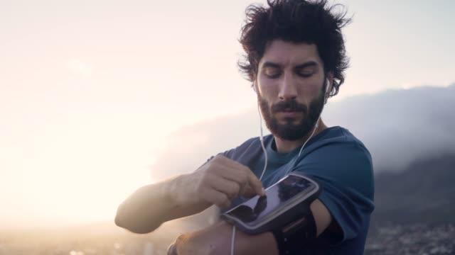 彼のトレーニング服の若い白いブルネットの男は、サンライズで彼のアームバンドに彼の携帯電話をチェック - スポーツ用品点の映像素材/bロール