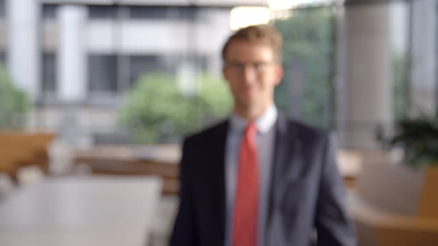 Young white businessman walking into focal plane video