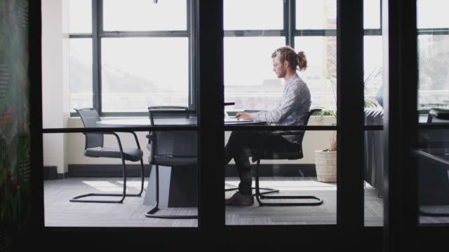 junger weißer geschäftsmann mit pferdeschwanz, der allein in einem büro arbeitet, durch glaswand gesehen, zoomen in - mann tür heimlich stock-videos und b-roll-filmmaterial