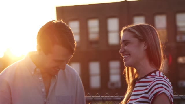 Young white couple talking on a Brooklyn rooftop at sunset Young white couple talking on a Brooklyn rooftop at sunset face to face stock videos & royalty-free footage