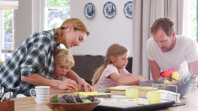 stockvideo's en b-roll-footage met jonge witte familie drukke samen in hun keuken, close-up - breakfast table