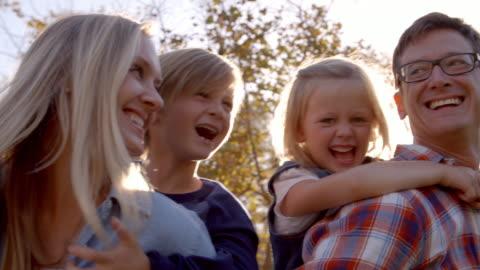 junge weiße familie mit spaß piggbacking in einem park - europäischer abstammung stock-videos und b-roll-filmmaterial