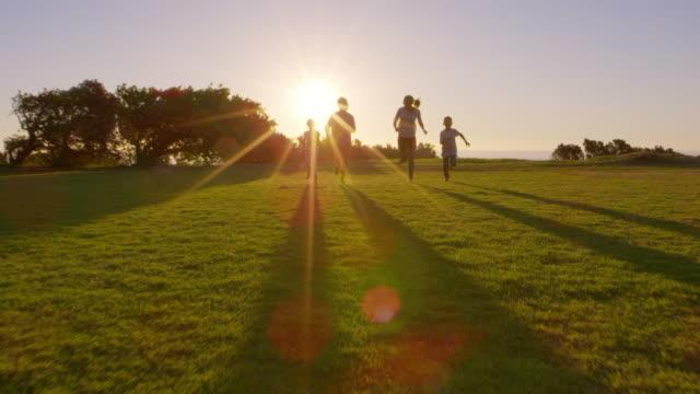 公園内移動カメラに向かって実行している若いホワイト家族 ビデオ