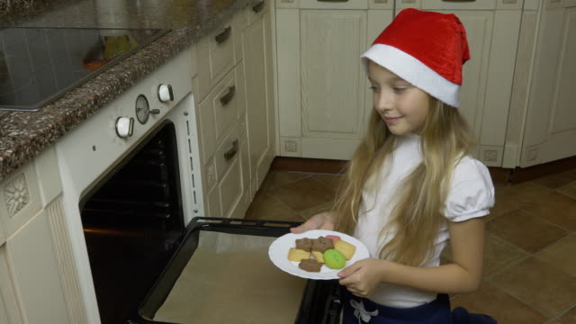 A young white girl dropped the cookies from the plate to the oven. A girl in a red cap prepares for Christmas. The girl bakes ginger biscuits cookies. video