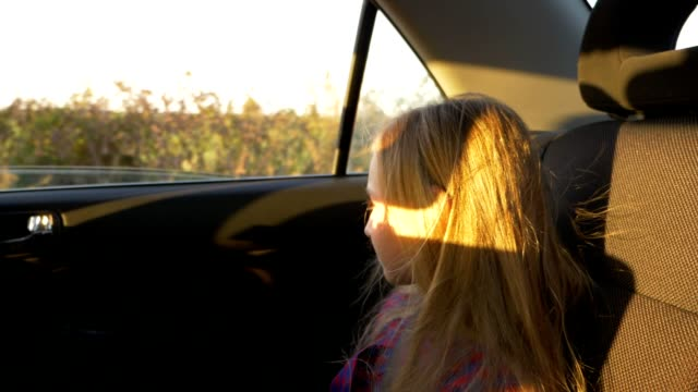 Young white girl sitting in car and jumping jolting on bumps. Slow motion close up handheld shot. video
