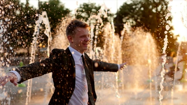 Young White Man Dancing in the Rain. Celebrating Business Career Success. Happy Guy Partying in a Water Fountain at Dusk. Banking, Finance, Trade, Economy. video