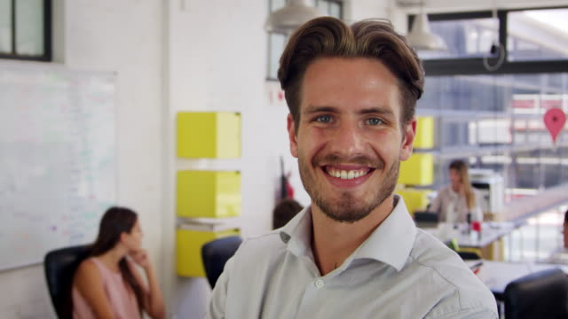 Young white man in office walks into focus and smiles video