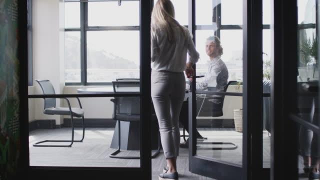 junge weiße frau tritt in einem besprechungsraum zu einem vorstellungsgespräch an, das durch glaswand gesehen wird - mann tür heimlich stock-videos und b-roll-filmmaterial