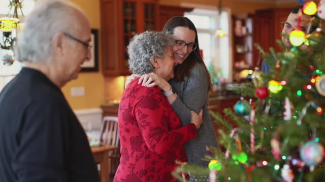 Young woman, a daughter, showing her love - hugging and kissing her senior mother, when the big two-generation family decorating a Christmas Tree in Christmas Eve