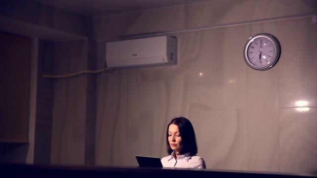 Jovem mulher administrador na recepção do hotel Dar as chaves está a trabalhar num tablet - vídeo