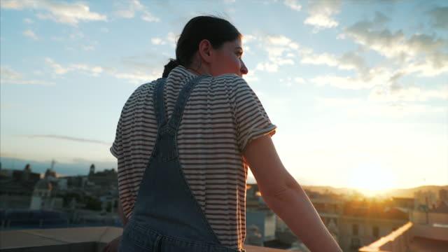 junge frau bewundert die stadtansicht. - dachgarten videos stock-videos und b-roll-filmmaterial