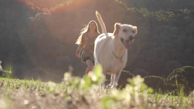 Young woman and her dog running on nature