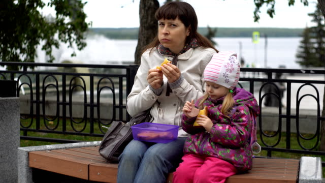 Young woman and her little daughter eating sandwiches in the park autumn. video