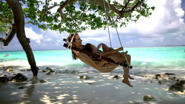 Mulher jovem e sua filha desfrutar de um pouco de descanso em uma rede sobre um praia tropical ao som das ondas. - vídeo