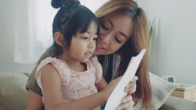 Young woman and her little girl viewing postcard at home.