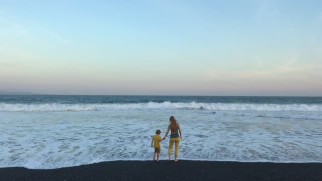A young woman and her little son on an ocean coast with black volcanic sand. Shot on a phone A young woman and her little son on an ocean coast with black volcanic sand. Shot on a phone. big island hawaii islands stock videos & royalty-free footage