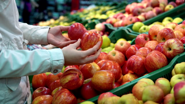 Young woman and little girl selects apples in the supermarket.