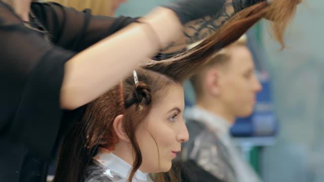 junge frau und mann bei friseursalon - haartönung stock-videos und b-roll-filmmaterial