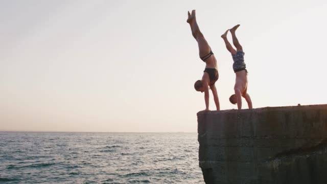 young woman and man jumping from a pier into the sea and doing tricks during beautiful sunrise, slow motion - alto video stock e b–roll