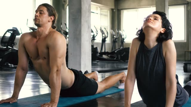 Young woman and man practicing yoga with upward dog and downward dog pose on the gym floor. Two people couple working out indoors