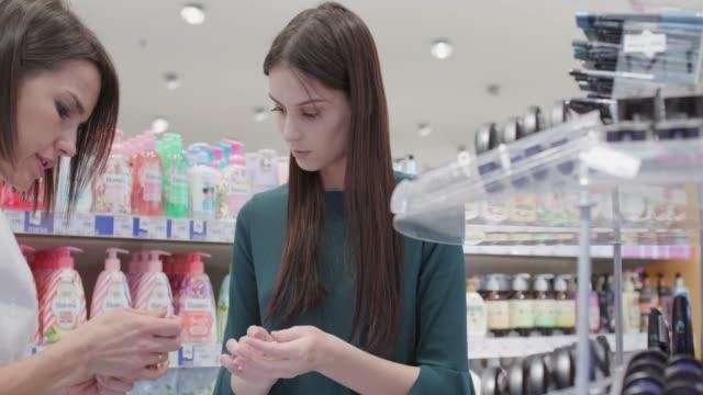 junge frau und verkäuferin vergleichen make-up - kosmetik beratung stock-videos und b-roll-filmmaterial