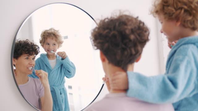 鏡を見て浴室で歯を磨く若い女性と小さな男の子 - ブラシ点の映像素材/bロール