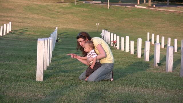 young woman and son visit grave hd - minnesmärke bildbanksvideor och videomaterial från bakom kulisserna