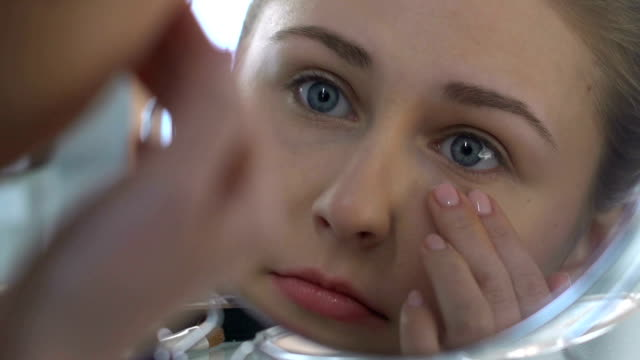 Young woman applying eye cream, anti-age cosmetic, skin care, rejuvenation video