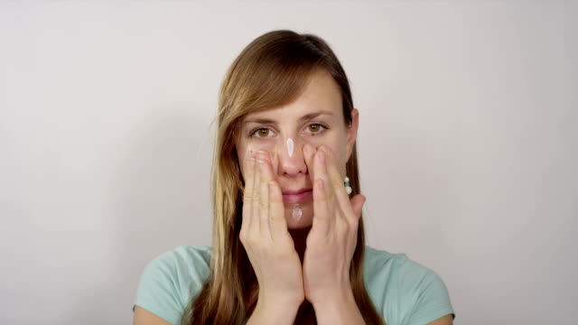 Young woman applying face moisturizer video