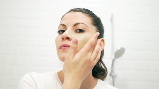 young woman applying facial mask on her skin. - facial stock videos & royalty-free footage