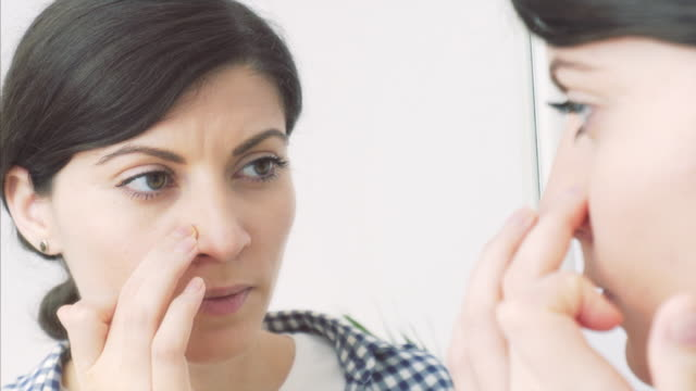 Young woman applying facial moisturizer. video