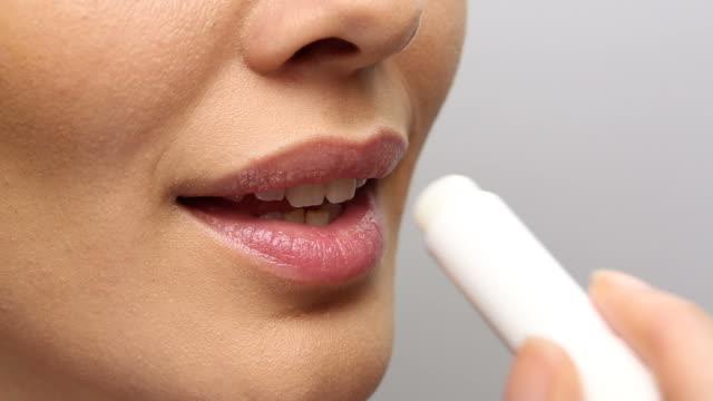 CU of young woman applying lip balm, she smiles. CU of young woman applying lip balm, she smiles. Static studio shot. lip balm stock videos & royalty-free footage